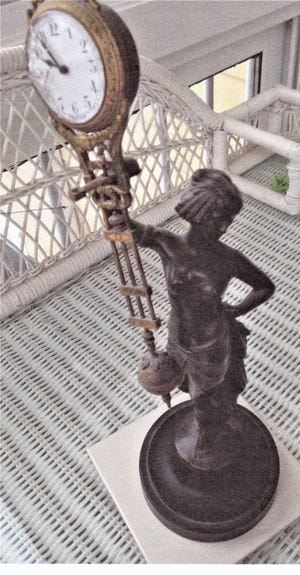 The figural swinging ball clock is likely made of spelter, a a white metal usually with a brass or bronze applied finish. [SUBMITTED PHOTO]