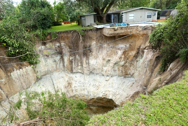 The swimming pool of a home cantilevers over a large sinkhole in the West End Estates neighborhood of Gainesville on Oct. 26, 2020. [Brad McClenny/The Gainesville Sun, File]