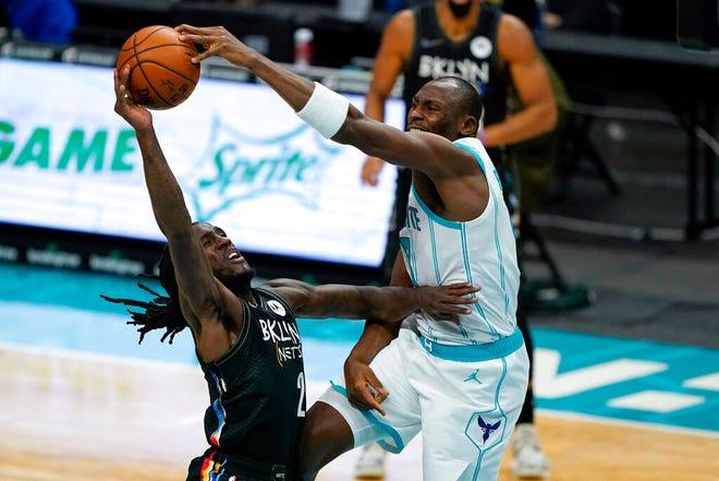 Charlotte Hornets center Bismack Biyombo blocks a shot by Brooklyn Nets forward Taurean Prince, left, during the first half of an NBA basketball game in Charlotte, N.C., Sunday, Dec. 27, 2020. (AP Photo/Chris Carlson)