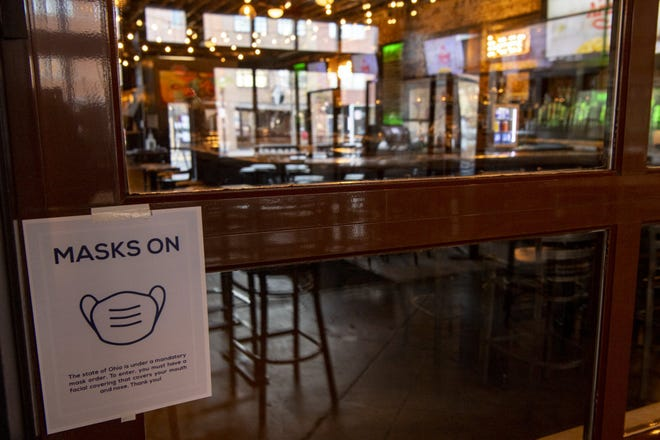 """A """"mask on"""" sign hangs inside Short North Pint House on North High Street in Columbus on Nov. 18."""