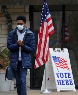 Lawrence University student Malcom Davis sanitizes his hands after voting at Memorial Presbyterian Church Tuesday, April 7, 2020, in Appleton, Wis.