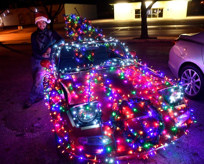 "James Mallon stands beside his1990 Mazda Miata, which he estimated is outfitted with ""two thousand-ish"" lights, parked outside of Mezamiz Coffee Shop on Dec. 21."