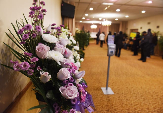 Guests wait inside the viewing room at Swanson Funeral Home at the visitation for Wayne County Sheriff Benny Napoleon on Monday, Dec. 28, 2020.