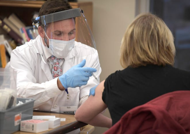 Pharmacist Nick Britt administers a COVID-19 vaccine to a staff member at Columbine West Health & Rehab Facility in Fort Collins, Colo. on Monday, Dec. 28, 2020.