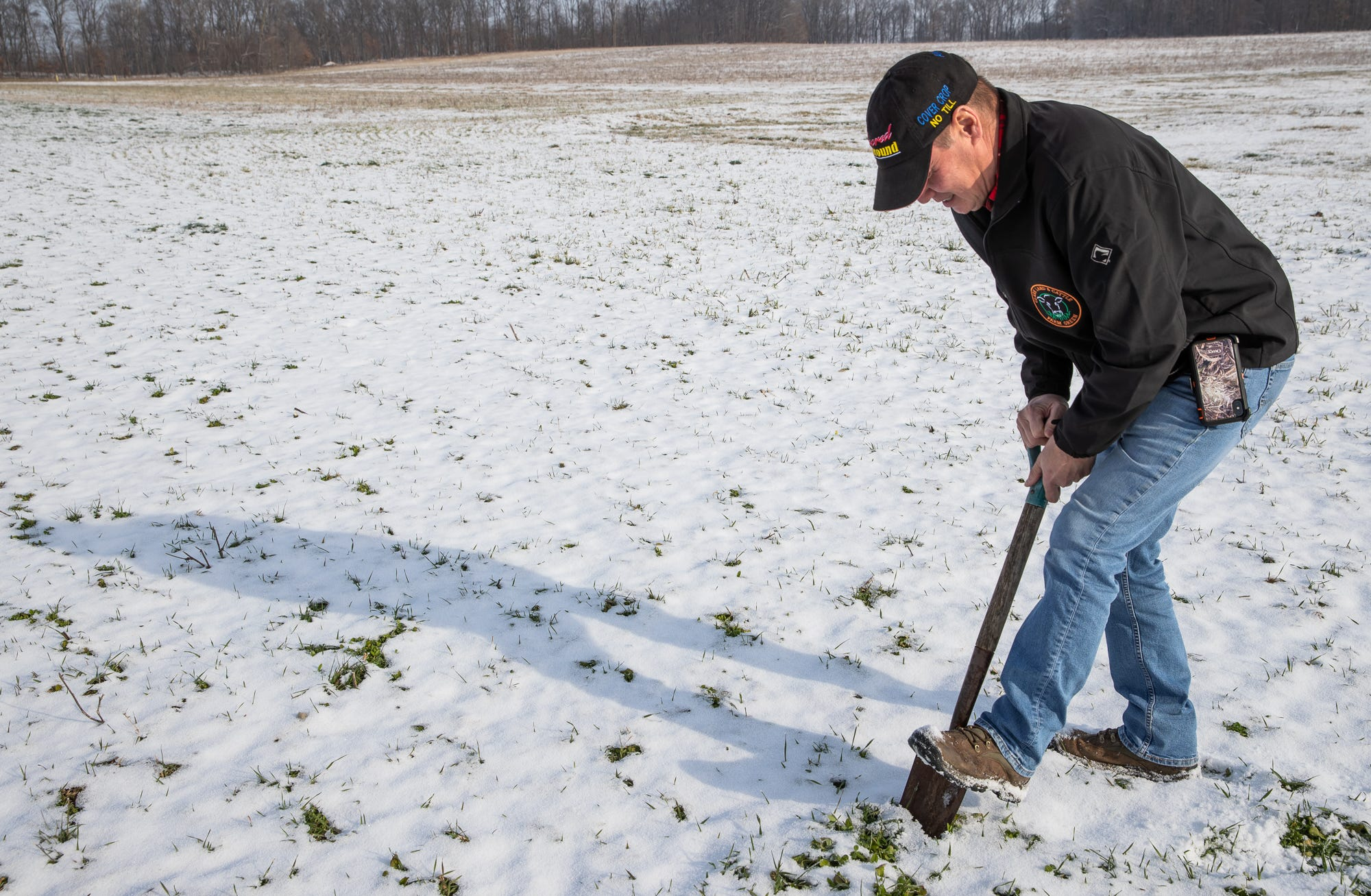 With snow on the ground on a chill day, farmer Rick Clark digs up a small batch of dirt from his field to see if he can find any earthworms at his farm in Williamsport, Ind., on Friday, Dec. 18, 2020. Clark is a regenerative agriculture farmer, focusing on soil health and removes chemicals and fertilizer from his fields.