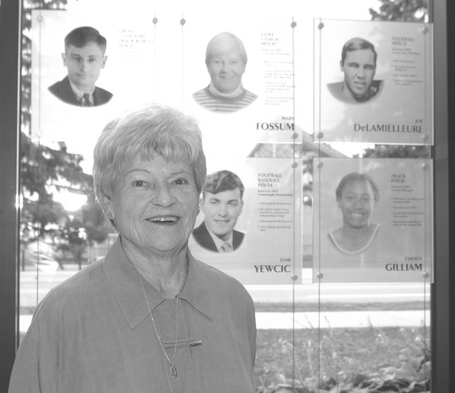 Mary Fossum, foreground, poses next to her plaque at the Michigan State Athletics Hall of Fame.