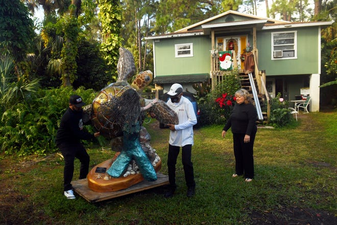 "The Source's executive director, Anthony Zorbaugh (left) and J.R. Gonzalez, prepare to move a fiberglass sea turtle to a waiting truck on Dec. 23, 2020, as artist Ruth Ann Holt looks on. The sculpture, originally designed and painted by Holt 15 years ago as part of the Mental Health Association's ""Turtle Trax - Overcoming Hurdles with Turtles"" project, is to be given to a person who donated $250,000 to The Source, which provides services to the homeless in Indian River County."