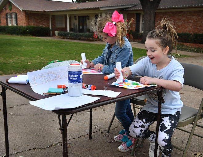 Arden Hoover, left, and Ellis Hodges make pictures using art supplies they received for Christmas. The five-year-olds were getting ready for an art show.