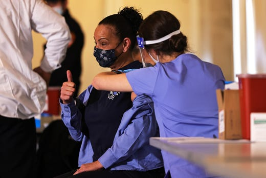 A member of FDNY EMS gives a thumbs up while receiving the coronavirus (COVID-19) vaccine on Dec. 23, 2020 in New York City. Members of FDNY EMS were given doses of the Moderna coronavirus (COVID-19) vaccine allotted for the department.