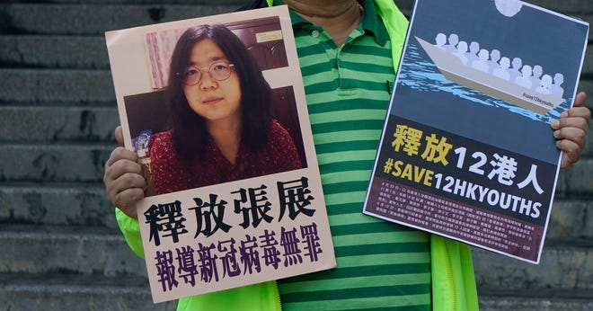 A pro-democracy activist holds placards with the picture of Chinese citizen journalist Zhang Zhan outside the Chinese central government's liaison office, in Hong Kong, Monday, Dec. 28, 2020. Zhang, a former lawyer and citizen journalist from Shanghai, has been sentenced to four years in prison for her reporting on the initial coronavirus outbreak in Wuhan, China. (AP Photo/Kin Cheung)