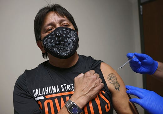 Tim King, a citizen of the Cherokee nation and a Cherokee language speaker, receives ther COVID-19 vaccine at the Cherokee Nation Outpatient Health Center Dec. 17, 2020, in Tahlequah, Okla. On his left arm is a tattoo of a dreamcatcher with the word Cherokee.
