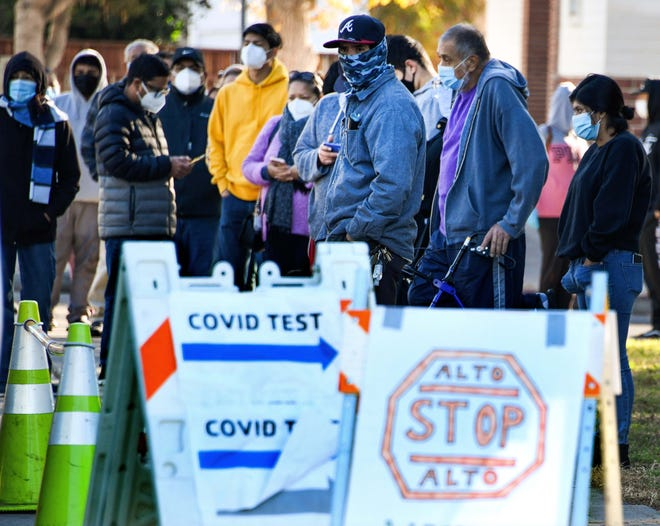 People wait in line to register for a COVID-19 test at a free walk-up testing site in Van Nuys, Calif. Los Angeles County and Los Angeles City are taking mobile COVID-19 testing to residents at pop-up testing sites in various neighborhoods in Los Angeles.