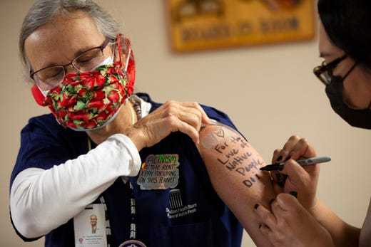 Dr. Theresa Maresca from the Seattle Indian Health Board (SIHB), lets a collegue write on her arm For the Love of Native People over the spot where she received a shot of the Moderna COVID-19 vaccine, at the SIHB, on Dec. 21, 2020 in Seattle, Wash. The Seattle Indian Health Board (SIHB) received 500 doses of the FDA-approved Moderna COVID-19 vaccine today.