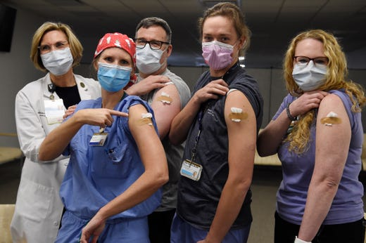 Chief Nursing Officer Robin L. Steaban, left, who administered the vaccine, stands with nurse practitioner Lisa Flemmons, Dr. Todd Rice, nurse Cody Hamilton and respiratory therapist Sophie Whitaker after they received a COVID-19 vaccine at Vanderbilt University Medical Center in Nashville, Tenn., Dec. 17, 2020.