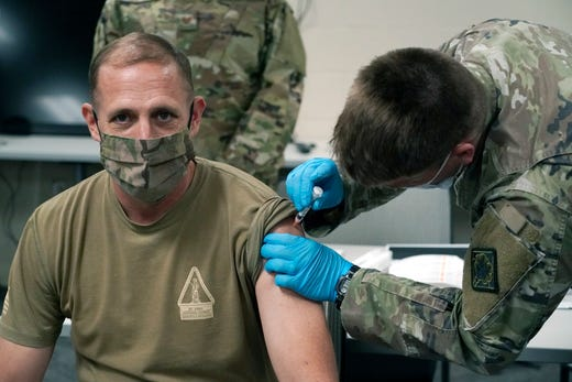 Command Sgt. Maj. John Raines of the Mississippi National Guard, looks away as he receives a dose of the Moderna COVID-19 vaccine in his arm, by a fellow guard member, Dec. 23, 2020, in Flowood, Miss. One hundred doses of the vaccine were administered to both Mississippi Air and Army National Guard service members who serve as first responders and currently assist with the administering of the COVID-19 test at Mississippi Department of Health drive through community testing sites across the state.