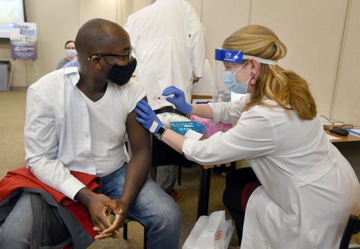 Dr. Cletus Oppong, who specializes in occupational medicine, is the first to receive the first round of the Moderna vaccine by Clinical Pharmacist Erin Conkright on  Dec. 24, 2020, at the Owensboro Health Regional Hospital in Owensboro, Ky.
