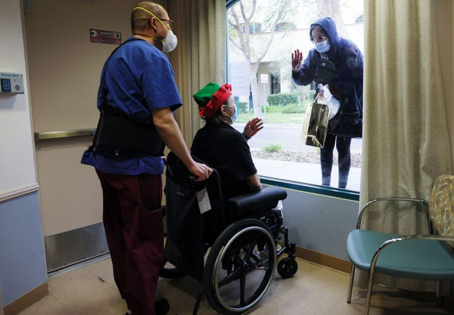 Juliet Babayan holds a gift for her sister Violet Bonyad as they visit through a window at the Ararat Nursing Facility on Christmas Eve on December 24, 2020 in Mission Hills, California.