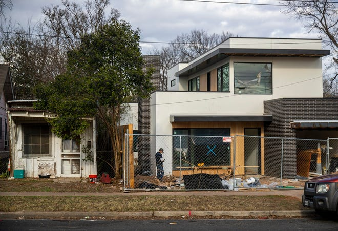 A new home goes up next to a smaller, older house on 11th Street in Austin on Dec. 28. A shift in the Austin City Council's power balance could lead to the council hammering out an agreement on rewriting the city's land use code.
