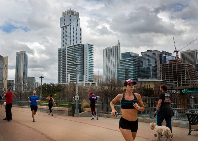 As storm clouds roll in Tuesday, joggers make their way across Pfluger Bridge over Lady Bird Lake in downtown Austin. A strong cold front will move into Central Texas from the northwest on Wednesday, forecasters say.