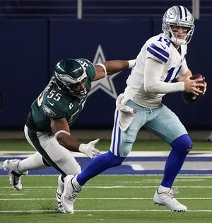 Dallas Cowboys quarterback Andy Dalton scrambles away from Philadelphia Eagles defensive end Brandon Graham during the Cowboys' blowout win Sunday. Dalton has led the team to three consecutive victories and has it on the doorstep of the postseason.