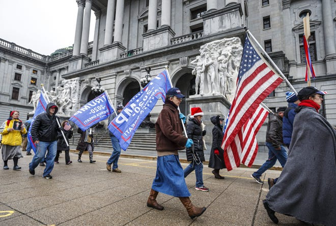 Supporters of President Donald Trump walk around the Capitol Complex in Harrisburg, Pa., as the electoral college convenes, Monday, Dec. 14, 2020. (Dan Gleiter/The Patriot-News via AP)