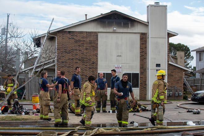 Several firefighters from the Austin Fire Department gather in front of a burnt multi-family building located on Wentworth Drive in Northeast Austin on Tuesday. Five residents and three dogs were evacuated from the building.