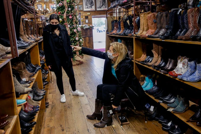 Linda Latushka, right, from New Jersey, points to a pair of cowboy boots while shopping Black Friday sales with her daughter, Lauren, at Allens Boots on South Congress Avenue. Retail activity in Texas flattened in December, according to a new report by the Dallas Federal Reserve.