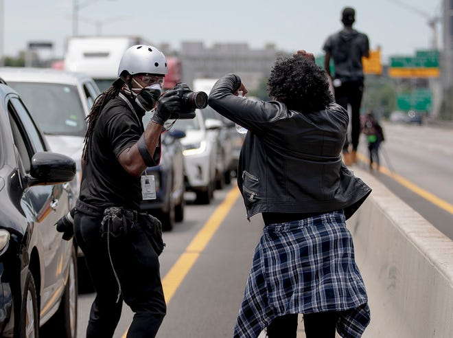 American-Statesman photojournalist Ricardo Barzziell photographs protesters on Interstate 35 during the May 30 demonstrations against police violence.