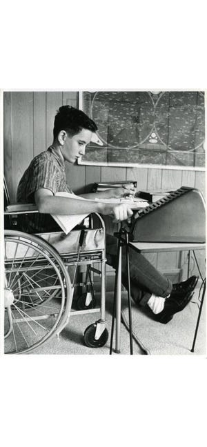 Mark Palchick, 12, sits in a wheelchair in 1962 in his Akron home while using a special machine to participate in classes.