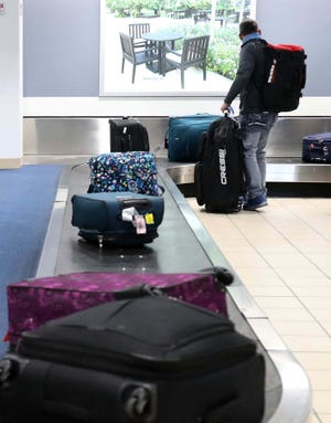 Passengers pick up their luggage at the Akron-Canton Airport Tuesday, Dec. 29, 2020 in Green, Ohio.