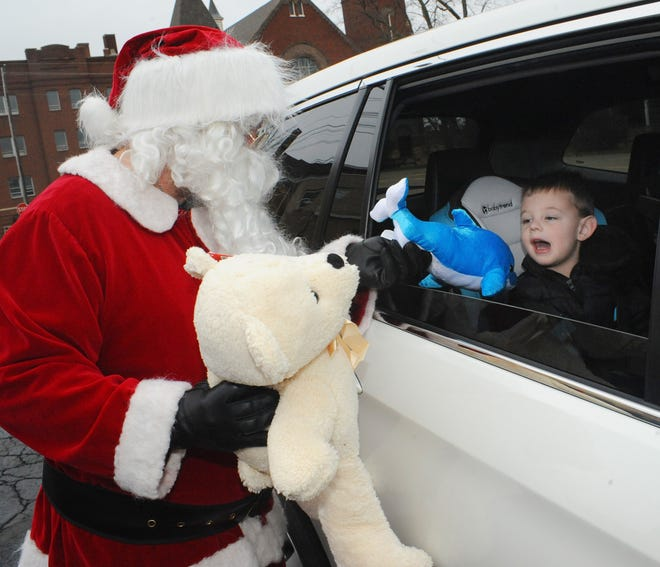 Maddox Morgan, 3, reacts as he receives a dolphin and teddy bear stuffed animal from Santa Claus during the Teddy Bear Drive-Thru Giveaway at St. Joseph Catholic Church.
