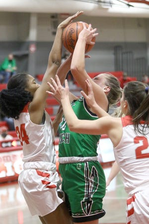 West Branch's Sydney Mercer, center, goes up for a shot defended closely by Minerva's Anissa Williams, left, and Coletta Miller, right, during conference action at Minerva High School Monday, December 28, 2020.