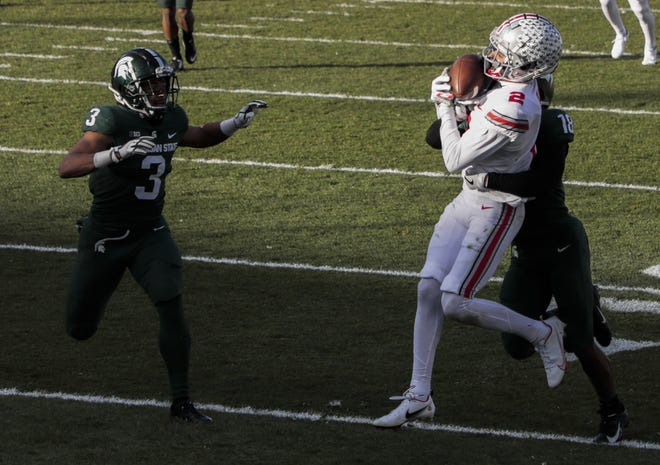 Ohio State receiver Chris Olave (2) hauls in a pass in a Dec. 5 game at Michigan State. Olave missed the Buckeyes' win over Northwestern in the Big Ten championship game because of COVID-19 but is expected to play against Clemson in the Sugar Bowl.