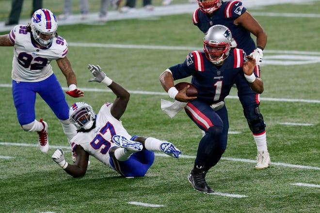 New England Patriots quarterback Cam Newton (1) runs from Buffalo Bills defensive ends Darryl Johnson (92) and Mario Addison (97) during Monday's game in Foxboro.