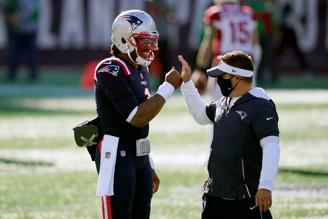 New England Patriots quarterback Cam Newton, left, greets offensive coordinator Josh McDaniels before a Nov. 29 game against the Arizona Cardinals in Foxboro.