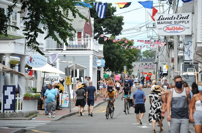 Visitors wearing masks walk along Commercial Street in Provincetown this past summer. Many expect wearing masks and other COVID-19 protocols will remain in effect this coming tourist season.