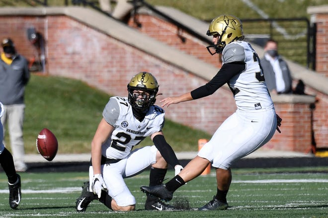 Vanderbilt's Sarah Fuller, right, kicks off as Ryan McCord (27) holds to start a Nov. 28 game against Missouri in Columbia, Mo. With the kick, Fuller became the first female to play in a Southeastern Conference football game.
