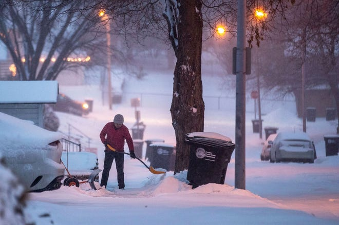Joachim Nguyen shovels snow in the early morning hours in Midtown Omaha, Neb., on Tuesday.