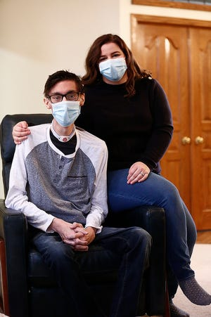 Austin Mooney and his wife Larisa relax at Austin's parents' house in Hilliard. Austin, 25, underwent a rare heart and double-lung transplant in June and then had life-threatening complications that kept him hospitalized for more than five months.