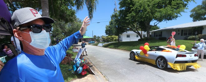 Wayne Walker, a coronavirus survivor who spent 8 weeks in the hospital, waves to passing cars parading past his Ormond Beach home, Sunday afternoon on May 17. News-Journal reporters and editors recall the year when COVID-19 dominated everything.