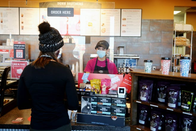 Armando Osornio, an employee at Dunn Brothers Coffee, takes a customer's order Dec. 22 at 1105 Lawrence Drive in Burlington.