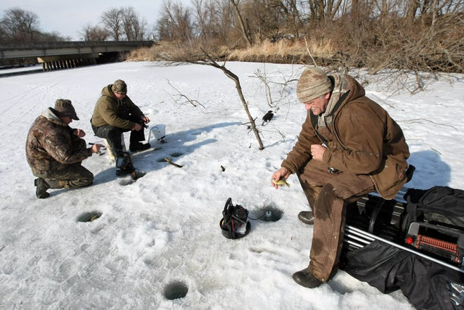 In this file photo fisherman, from left, Jared Bloom, R.J. Truitt, fish as Stan Woodard, all of Muscatine, throws back a baby bluegill while ice fishing on a backwater slough north of Wapello.