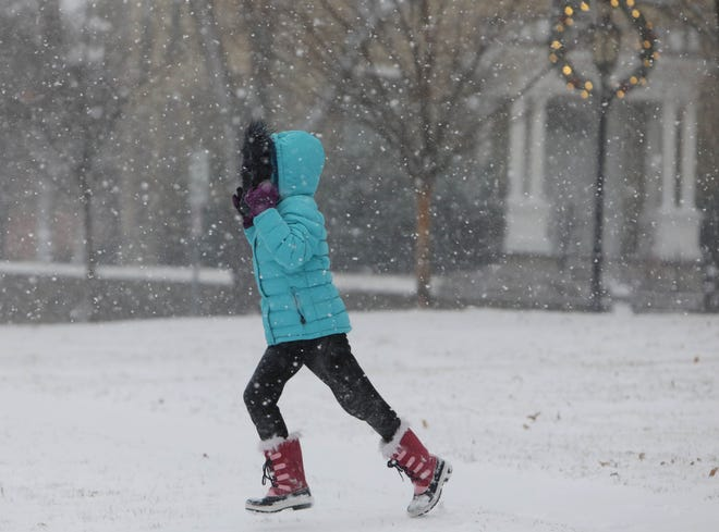 A child makes her way from North Hill park Dec. 29 after playing in the falling snow as a winter storm dumps snow and ice Southeast Iowa in Burlington. More winter weather is expected for the region tonight into Sunday morning, as well as Monday and Wednesday.