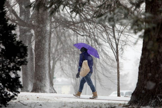 A pedestrian uses an umbrella to keep the snow away Tuesday as she crosses North Hill Park in Burlington.
