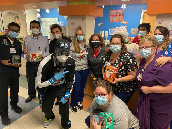 Christian rapper Brinson (foreground, left) poses with members of the pediatric team at Orange Park Medical Center after bringing coffee and sweets to show his appreciation for their frontline work.