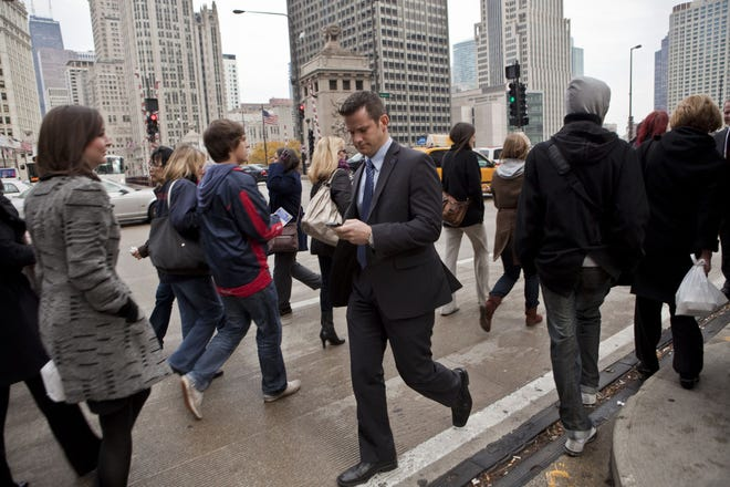 Adam Kinzinger reads his email as he walks along Michigan Avenue during visits to Chicago television stations the day after his election night victory on Nov. 3, 2010.