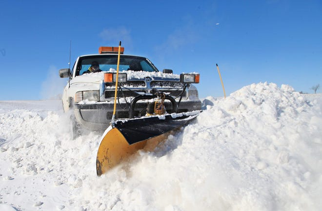 In this Jan. 28, 2014, file photo, Snow Pros owner Rob Chambers clears drifts from a driveway in the Freeport area.