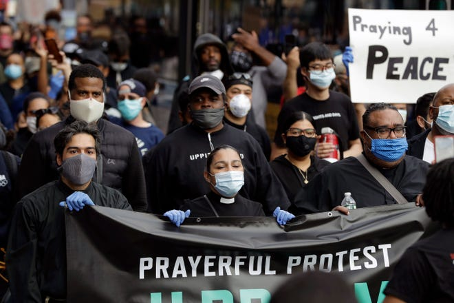 In this June 2, 2020, file photo, members of the clergy lead protesters in the Prayerful Protest march for George Floyd, in the Brooklyn borough of New York. Floyd died after being restrained by Minneapolis police officers on Memorial Day, May 25. During nationwide protests, leaders from many religious traditions spoke out to support the peaceful goals of demonstrators.