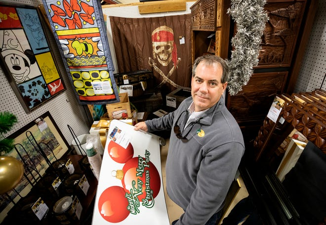 Eric Zinkann owner of Vault Collectibles, holds a Disney sign at his booth in the Lakeland Antique Mall in Lakeland. Zinkann is part of an exclusive club - sellers who can deal directly in collectible goods from Disney parks and hotels.