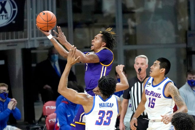 Western Illinois' Anthony Jones drives to the basket past DePaul's Pauly Paulicap (33) and Oscar Lopez Jr. during the first half of an NCAA college basketball game Wednesday, Dec. 23, 2020, in Chicago. [AP Photo/Charles Rex Arbogast]